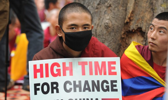 Tibetans monks hold placards during a protest rally in New Delhi on January 31, 2013. The Chinese regime has deployed a new surveillance system, which will make it more difficult for Tibetans to escape to Nepal. (Raveendran/AFP/Getty Images)