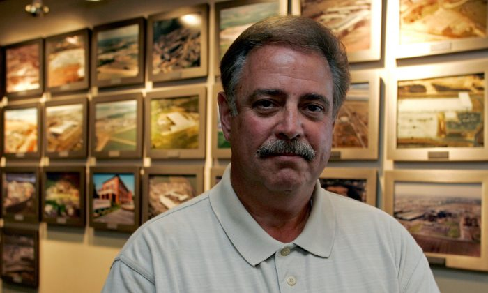 Dan DiMicco, chairman emeritus of Nucor Corp., stands near photos of the company's steel plants at the company's headquarters in Charlotte, N.C., on July 18, 2006. (AP Photo/Chuck Burton)