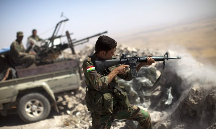 An Iraqi Kurdish Peshmerga fighter fires at ISIS militant positions, from his position on the top of Mount Zardak, a strategic point about 15.5 miles (25 km) east of Mosul on Sept. 9, 2014. (J.M. Lopez/AFP/Getty Images)