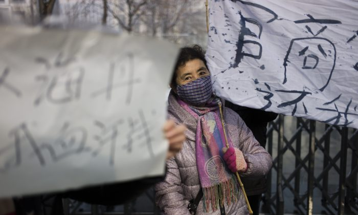A woman holds up a banner as a group protests about alleged local government wrongdoing and unpaid wages outside the Langfang Court on Dec. 10, 2014. (Fred Dufour/AFP/Getty Images)
