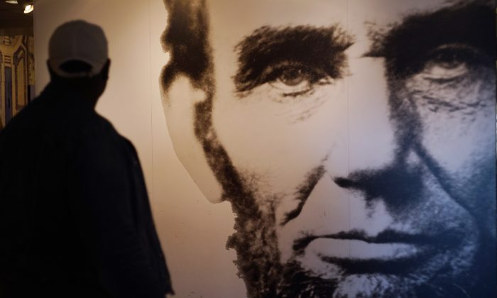 A visitor to an exhibit at the Lincoln Memorial walks past an image of Abraham Lincoln in Washington, D.C., on April 1, 2015. (Mandel Ngan/AFP/Getty Images)