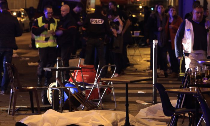 A victim is pictured on the pavement outside a Paris restaurant, Friday, Nov. 13, 2015. (AP Photo/Thibault Camus)