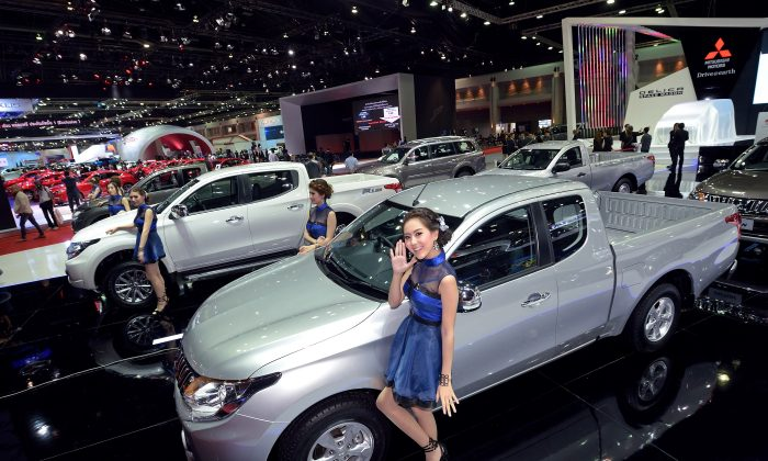 Models pose next to cars displayed at the 36th Bangkok International Motor Show on March 24, 2015. The 36th Bangkok International Motor Show will be held until April 5. AFP PHOTO / PORNCHAI KITTIWONGSAKUL        (Photo credit should read PORNCHAI KITTIWONGSAKUL/AFP/Getty Images)