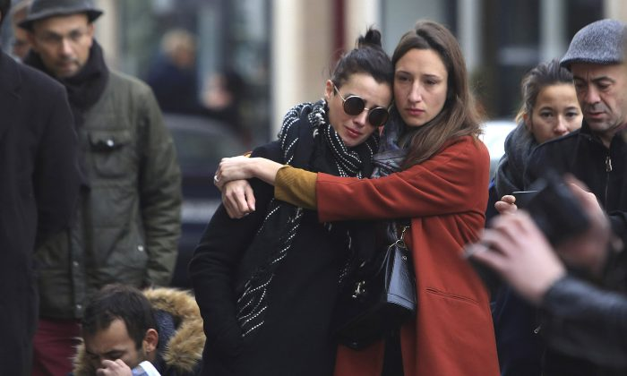 Women comfort each other as they stand in front of the Carillon cafe, in Paris, Saturday, Nov.14, 2015. French President Francois Hollande vowed to attack Islamic State without mercy as the jihadist group admitted responsibility Saturday for orchestrating the deadliest attacks inflicted on France since World War II. (AP Photo/Thibault Camus)