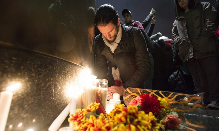 """People light candles at a vigil outside the French consulate in Montreal, Friday, Nov. 13, 2015. Canadian Prime Minister Justin Trudeau offered """"all of Canada's support"""" to France on Friday night in the wake of """"deeply worrying"""" terrorist attacks in Paris. (Graham Hughes/The Canadian Press via AP)"""