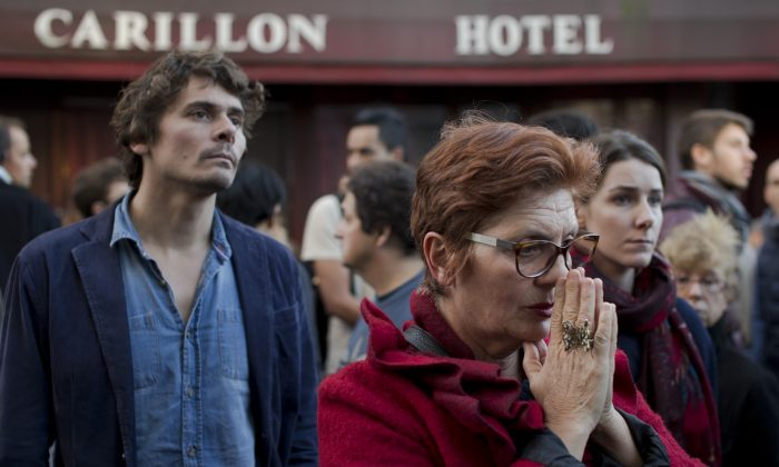 People pay their respect to the victims of the the attacks on restaurant Le Petit Cambodge (Little Cambodia) and the Carillon Hotel, rear, on the first of three days of national mourning in Paris, Sunday, Nov. 15, 2015. (AP Photo/Peter Dejong)