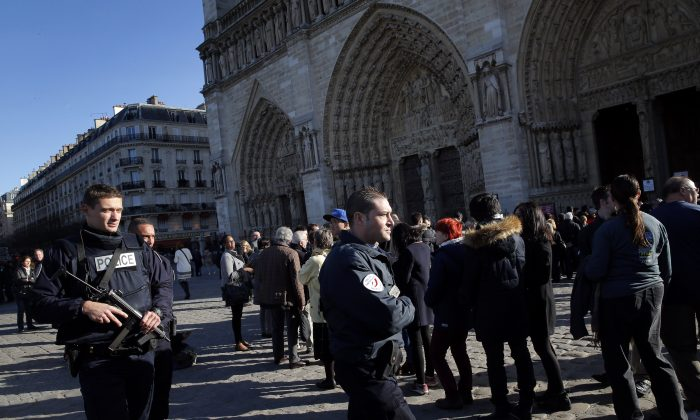 """Authorities cleared the Republique plaza, or the Place de la République is a square in Paris, after unconfirmed reports of """"gunshots,"""" where mourners were gathering for the dead in the terrorist attacks that left at least 128 dead in Paris.  (AP Photo/Christophe Ena)"""