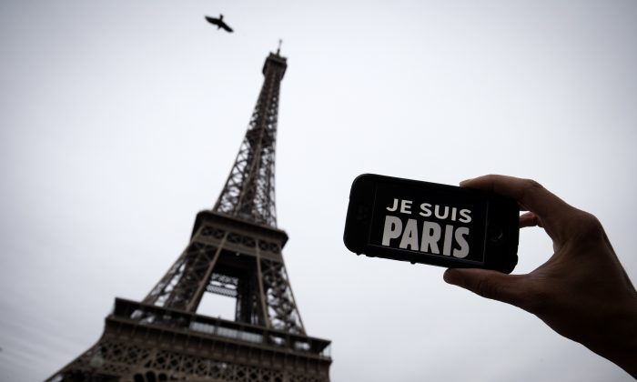 """In this illustration picture taken in Paris on November 14, 2015 a person holds aloft a smartphone bearing the message """"Je Suis Paris"""" in front of the Eiffel Tour, following a series of attacks on the city in which at least 128 people were killed.  Islamic State jihadists on Saturday claimed a series of coordinated attacks by gunmen and suicide bombers in Paris that killed at least 128 people in scenes of carnage at a concert hall, restaurants and the national stadium.  AFP PHOTO / JOEL SAGET        (Photo credit should read JOEL SAGET/AFP/Getty Images)"""