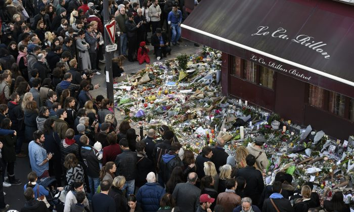"People gather at a makeshift memorial in front of ""Le carillon"" restaurant on Nov. 16, in the 10th district of Paris, following a series of coordinated terrorists attacks on Nov. 13. (Alain Jocard/AFP/Getty Images)"