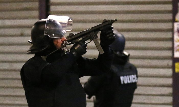 Police forces prepare in Saint-Denis, a northern suburb of Paris, Wednesday, Nov. 18, 2015. Authorities in the Paris suburb of St. Denis are telling residents to stay inside during a large police operation near France's national stadium that two officials say is linked to last week's deadly attacks. (AP Photo/Francois Mori)