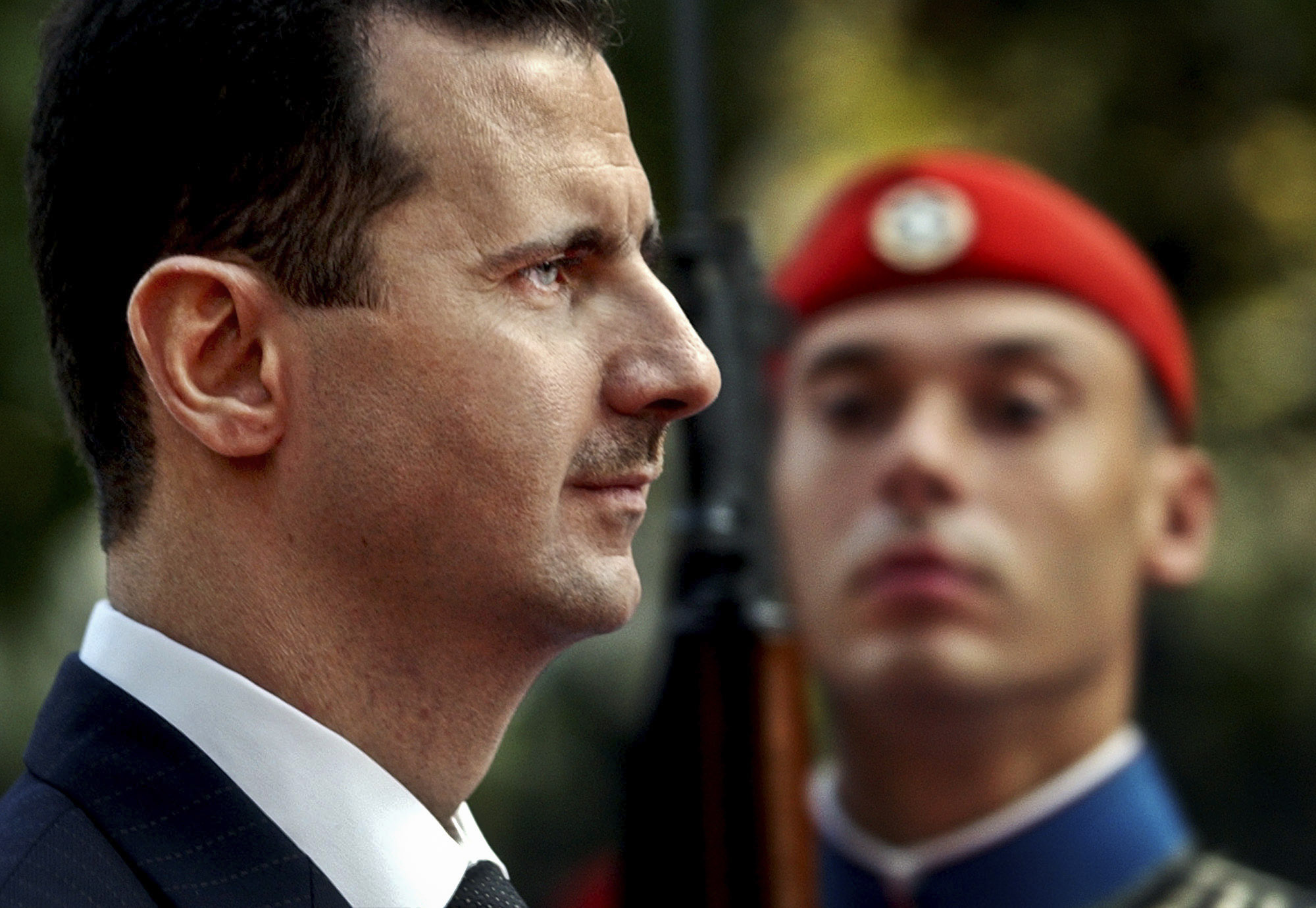 Syrian President Bashar Assad reviews the presidential guard during a welcoming ceremony in Athens on Dec. 15, 2003. (AP Photo/Petros Giannakouris)