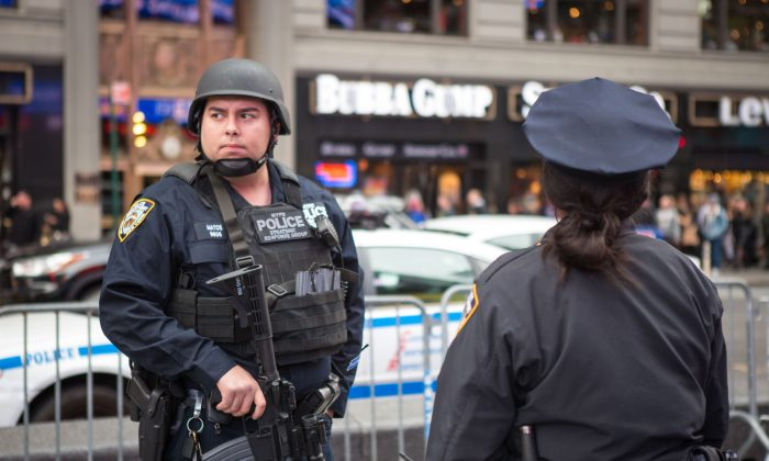 A Member of the NYPD Strategic Response Group and an NYPD officer stand guard in New York's Times Square on Nov. 18, 2015. Police officials said they've deployed extra units to crowded areas of the city in the wake of the Paris terror attacks. (Benjamin Chasteen/Epoch Times)