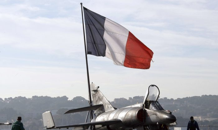 French sailors walk by a Super-Etendard jetfighter on the deck of France's nuclear-powered aircraft carrier Charles de Gaulle before leaving the port of Toulon on Nov. 18, 2015. (AP Photo/Claude Paris)