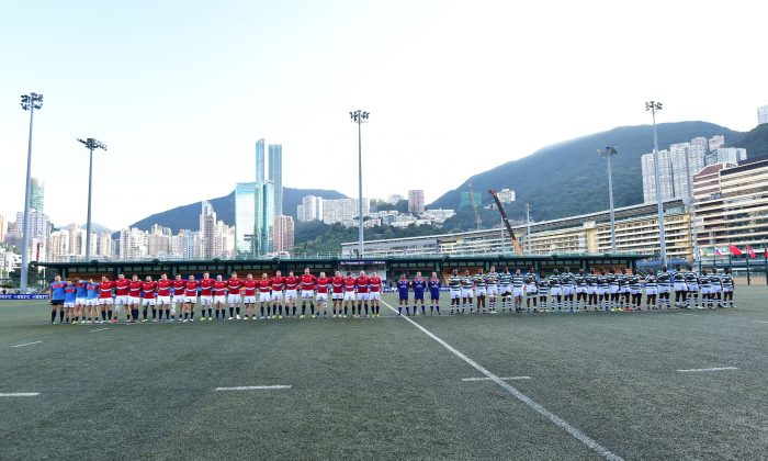 Teams line up before the start of the match between Russia (red) and Zimbabwe (green hoops) in the Cup of Nations in Hong Kong on Tuesday Nov 17, 2015. (Bill Cox/Epoch Times)