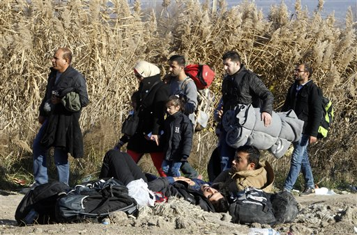 Migrants and refugees walk towards the border with Serbia, while other migrants, who were not allowed to cross into Serbia, lie on the ground awaiting for a solution, near the village of Tabanovce, in northern Macedonia, Thursday, Nov. 19, 2015. (AP Photo/Boris Grdanoski)