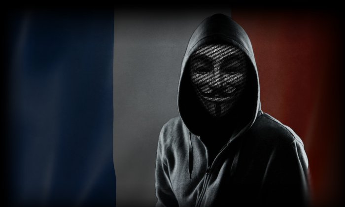 A hooded figure wears a Guy Fawkes mask in an image used by TorReaper, a member of the GhostSec anti-terrorism hacker group. GhostSec and the hacker collective Anonymous are fighting the online presence of ISIS. (GhostSec)