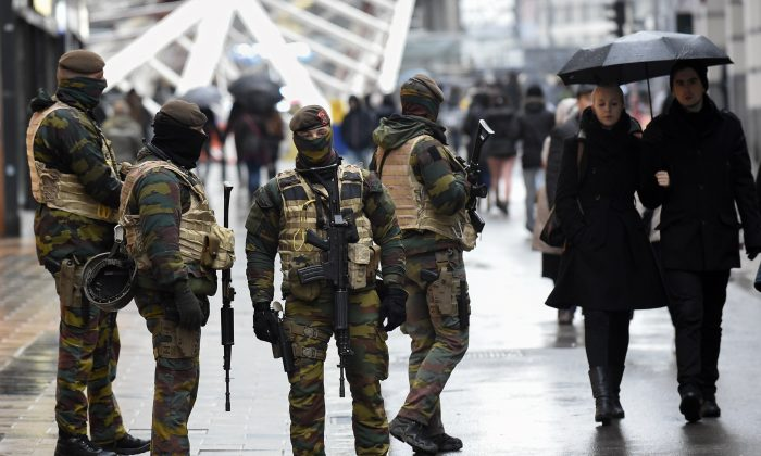 "Soldiers patrol the Rue Neuve pedestrian shopping street in Brussels on November 21, 2015. All metro train stations in Brussels will be closed on November 21, the city's public transport network said after Belgium raised the capital's terror alert to the highest level, warning of an ""imminent threat."" (AFP/Getty Images)"