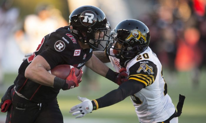 Ottawa Redblacks wide receiverGregEllingson fights off Hamilton Tiger-Cats defensive back Emanuel Davis as he runs for a touchdown in the fourth quarter in the CFL East Division final in Ottawa on Nov. 22, 2015. (The Canadian Press/Adrian Wyld)
