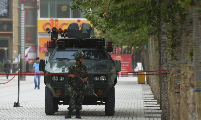 The undated photo shows a member of the Chinese paramilitary police in front of an armored vehicle in Hotan, Xinjiang region of China. The Chinese regime has deepened its suppression of the Uyghur ethnic group in the region. (Greg Baker/AFP/Getty Images)