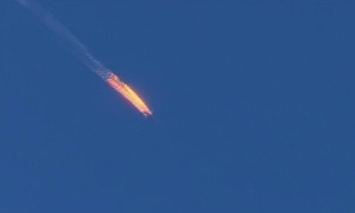 This frame grab from video by Haberturk TV, shows a Russian warplane on fire before crashing on a hill as seen from Hatay province, Turkey, Tuesday, Nov. 24, 2015. (Haberturk TV via AP)
