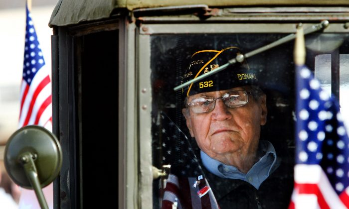 Korean War veteran Fred VanHoosier rides in a antique military truck during a Veterans Day parade in Davenport, Iowa, on Nov. 11, 2015. (Kevin E. Schmidt/Quad City Times via AP)