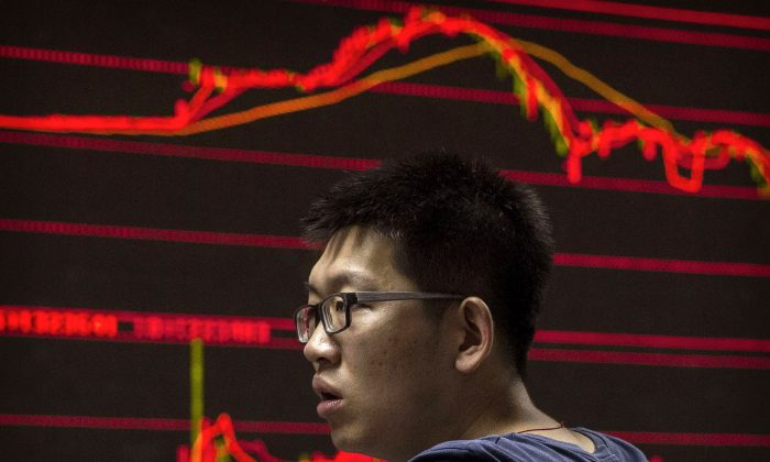 A Chinese day trader reacts as he watches a stock ticker at a local brokerage house in Beijing, China, on Aug. 27, 2015. (Kevin Frayer/Getty Images)