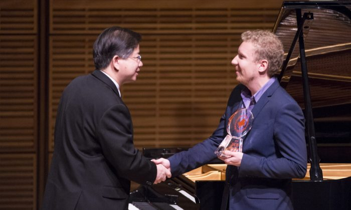 Pianist Anton Smirnoff receives the bronze award from NTDTV president Tang Zhong at the conclusion of the NTD Television's 2014 International Piano Competition at Carnegie Hall on Oct. 5, 2014. (Dai Bing/Epoch Times)