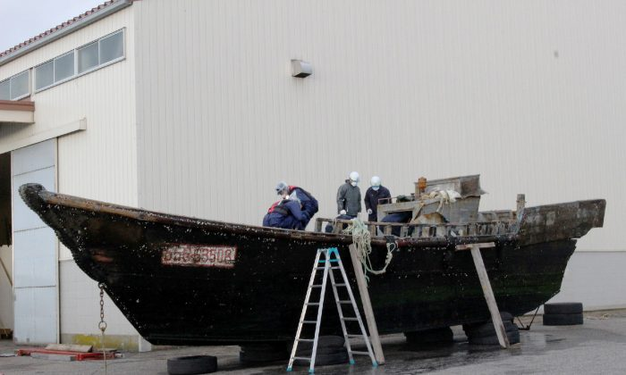 This picture taken on November 24, 2015 shows coast guard officials investigating a wooden boat at the Fukui port in Sakai city in Fukui prefecture, western Japan after the ship was found drifting off the coast of Fukui. Japan is investigating nearly a dozen suspicious boats recently found drifting off the country's coastline, some with decaying bodies aboard, officials said on November 27, as media speculated they came from North Korea. At least 11 cases involving wooden boats -- some badly damaged -- with 20 bodies on board have been reported during October and November.   (JIJI PRESS/AFP/Getty Images)