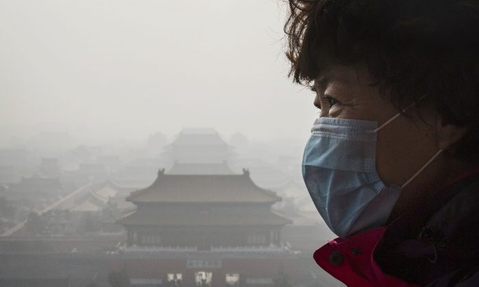 A Chinese woman wears a mask as haze from smog caused by air pollution hangs over the Forbidden City in Beijing, China, on Nov. 15, 2015.  (WHO). (Kevin Frayer/Getty Images)