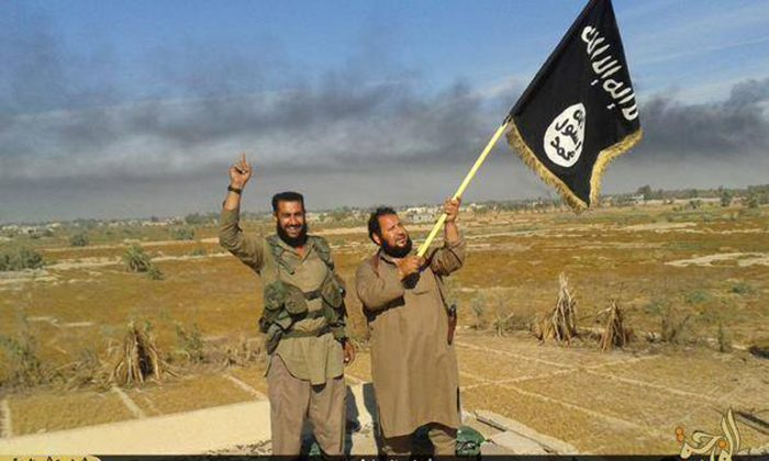 In this file photo released on Sunday, June 28, 2015, by a website of Islamic State militants, an Islamic State militant waves his group's flag as he and another celebrate in Fallujah, Iraq, west of Baghdad. (Militant website via AP, File)