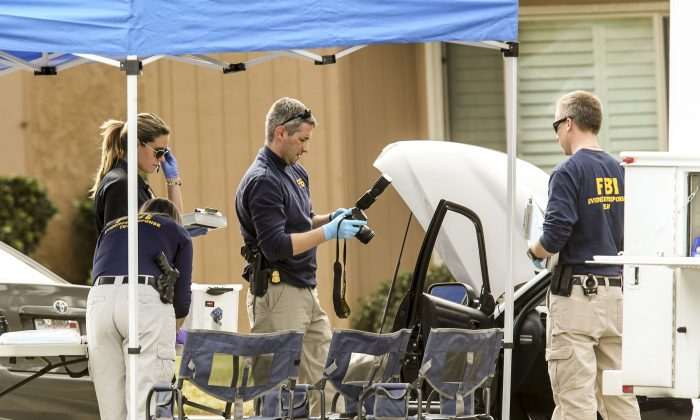FBI agents investigate a car near a home in connection to the shootings in San Bernardino, Thursday, Dec. 3, 2015, in Redlands, Calif. (AP Photo/Ringo H.W. Chiu)