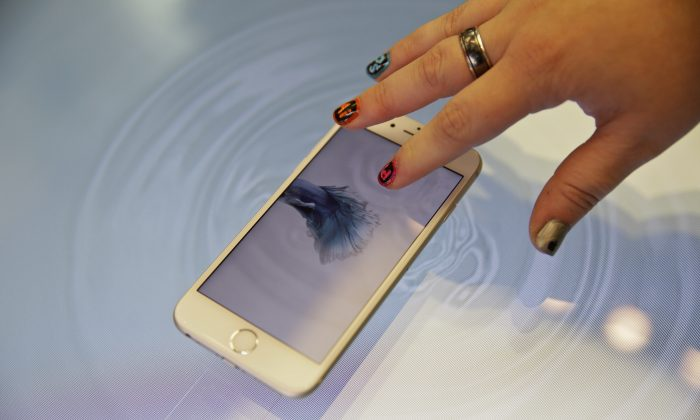 A woman presses an Apple iPhone 6s on a 3D touch table at the Apple store on  Nov. 13. (AP Photo/Eric Risberg)