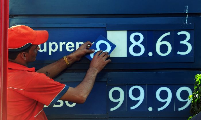 A Pakistani employee changes the oil prices on a billboard in Karachi on May 1, 2011. (ASIF HASSAN/AFP/Getty Images)