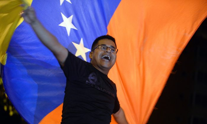 Venezuelan opposition supporters celebrate the results of the legislative election in Caracas, on Dec. 7, 2015. Venezuela's opposition won at least a majority of 99 out of 167 seats in the state legislature, electoral authorities said Monday, the first such shift in power in congress in 16 years. (Federico Parra/AFP/Getty Images)