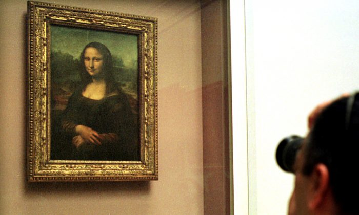 A man takes a photograph of The Mona Lisa painting, behind a protective glass, in the Louvre museum in Paris in a Monday April 26, 2004 file photo. (AP Photo/Amel Pain, File)