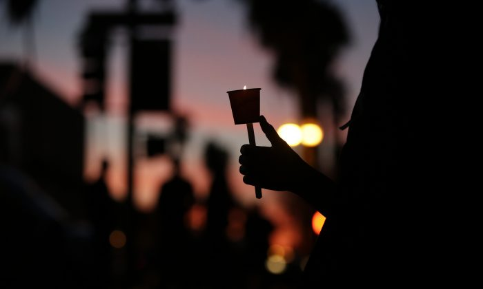 """Cathleen Garcia holds a candle during a vigil to honor shooting victims on Monday, Dec. 7, 2015, in San Bernardino, Calif. The husband and wife who opened fire on a social services center last week had been radicalized """"for quite some time"""" and had taken target practice at area gun ranges, in one instance just days before the attack that left 14 people dead, the FBI said Monday. (AP Photo/Jae C. Hong)"""