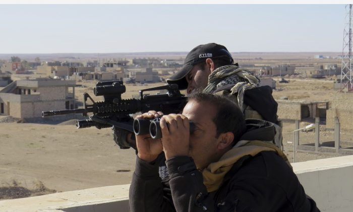 Soldiers of Iraq anti-terrorism forces watch movements during a military operation to regain control of the western suburbs of Ramadi, Anbar Province, Iraq, on Nov. 14, 2015.  (AP Photo/Osama Sami)