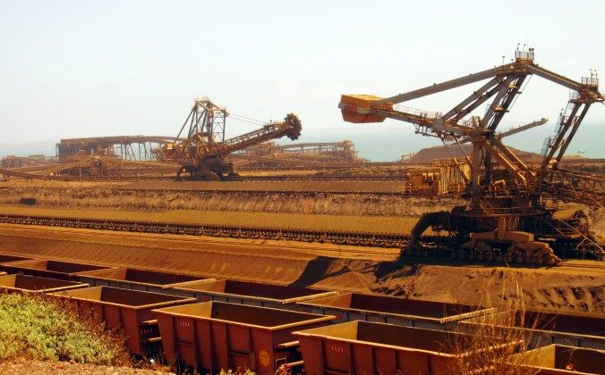Stackers and reclaimers move iron ore to rail cars at Rio Tinto's Port Dampier operations in Western Australia's Pilbara region. China's deepening slowdown is likely to have an outsize impact on Australian miners. (Amy Coopes/AFP/Getty Images)