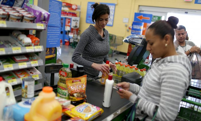 Walmart employee Darlin Cienfuegos rings up customer purchases at a Walmart store on Feb. 19, 2015 in Miami, Florida. (Joe Raedle/Getty Images)