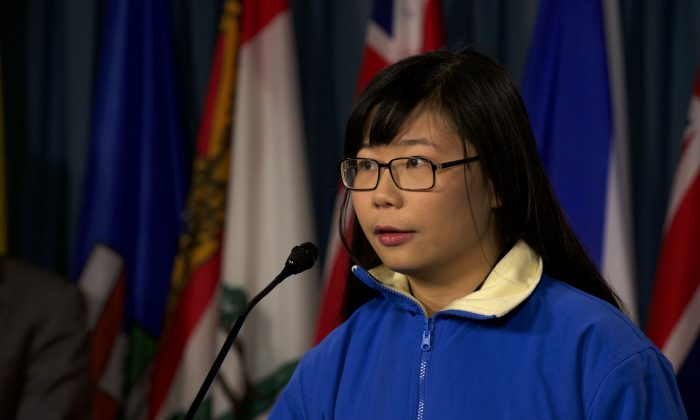 Hope Chen speaks to reporters on Parliament Hill on Dec. 9. The 22-year-old is trying to draw attention to the plight of her father who was imprisoned in China for suing former Chinese leader Jiang Zemin. Chen has been threatened by a Chinese agent for discussing his detention in the media. (Matthew Little/Epoch Times)