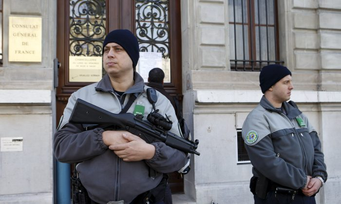 Security officers control the area in front of the  French consulate due to a high level of alert, in Geneva, Switzerland, Friday, Dec. 11, 2015. (Salvatore Di Nolfi/Keystone via AP)