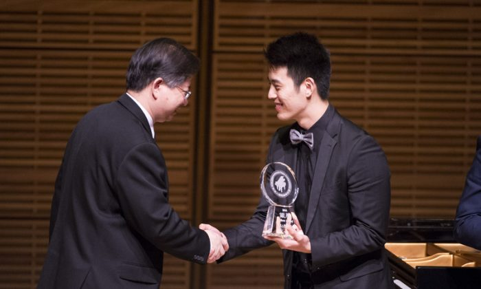 Pianist Joseph Choi receives the silver award from NTDTV president Tang Zhong at the conclusion of the NTD Television's 2014 International Piano Competition at Carnegie Hall on Oct. 5, 2014. (Dai Bing/Epoch Times)