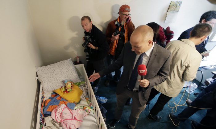 Members of the media crowd into the room that the baby of terrorists Syed Rizwan Farook and Tashfeen Malik lived in before her parents killed 14 people on December 2, 2015. (AP Photo/Chris Carlson)