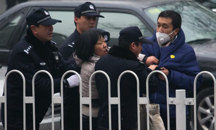 A supporter of rights lawyer Pu Zhiqiang scuffles with policemen near the Beijing Second Intermediate People's Court during Pu's trial in Beijing on Dec. 14, 2015. (AP Photo/Andy Wong)