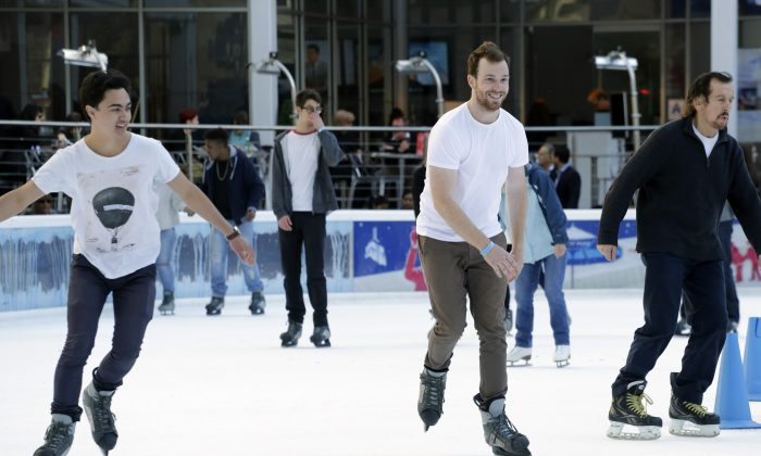 Men in T-shirts skate around the ice rink in Bryant Park, Tuesday, Dec. 15, 2015, in New York. The region is experiencing unseasonably warm weather this week. (AP Photo/Mark Lennihan)
