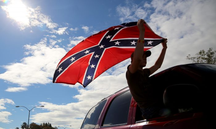 A man waves a Confederate battle flag as he drives away from Roseburg Regional Airport in Roseburg, Ore., on Oct. 9. (AP Photo/Ryan Kang)
