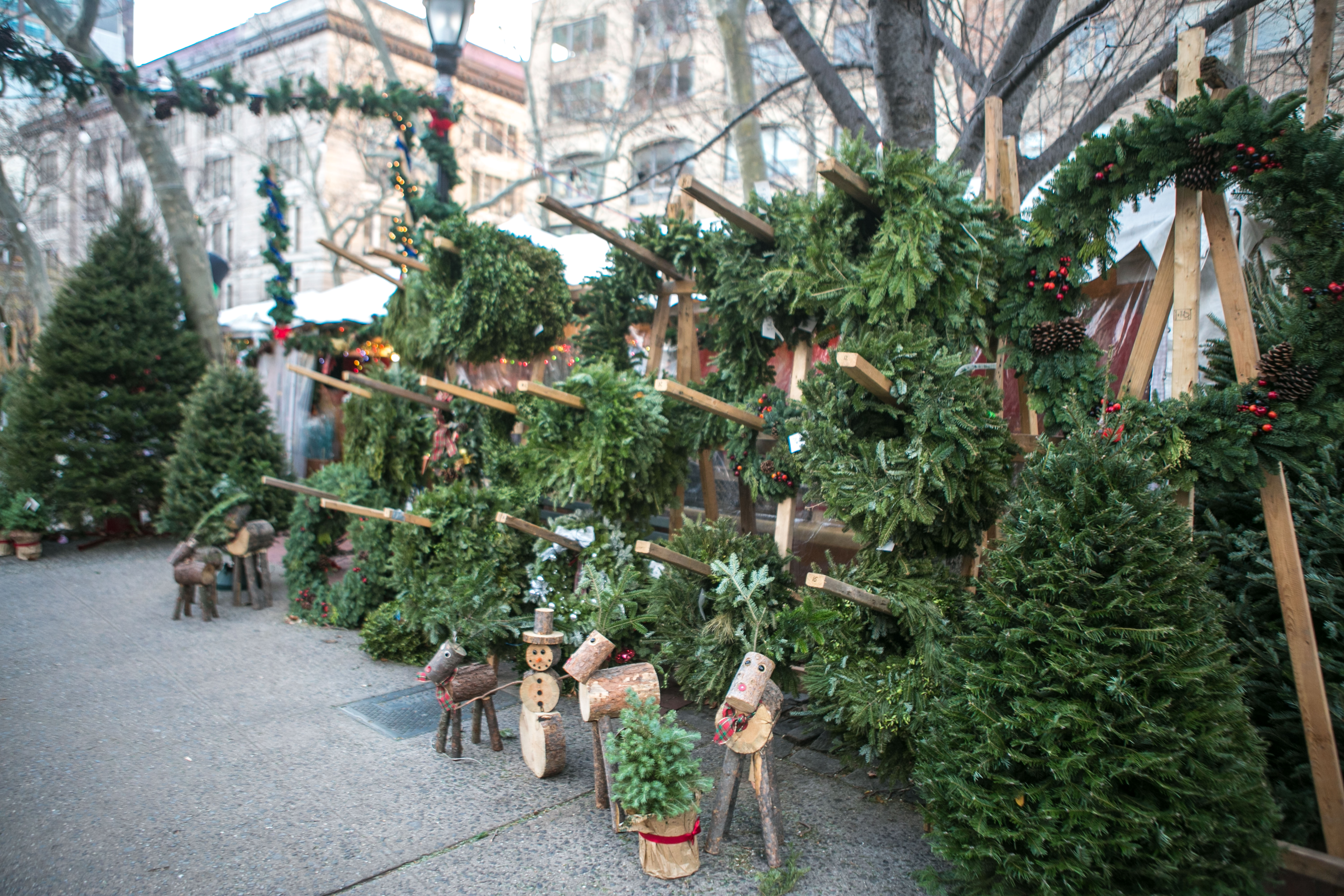 Christmas trees and wreaths for sale at a sidewalk pop-up holiday shop in the