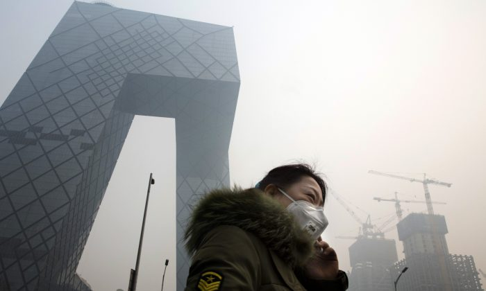 A woman wears a mask for protection against the pollution in Beijing, China, Wednesday, Dec. 9, 2015. Unhealthy smog hovered over downtown Beijing as limits on cars, factories and construction sites kept pollution from spiking even higher Wednesday, on the second of three days of restrictions triggered by the city's first red alert for smog. (AP Photo/Ng Han Guan)