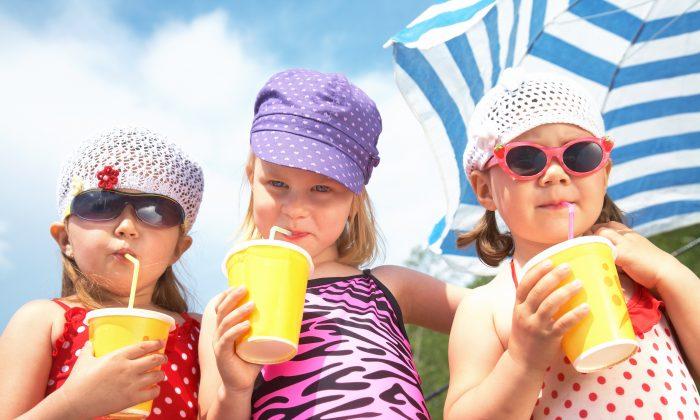 Three little cute girls drinking on the beach. (Fotolia)