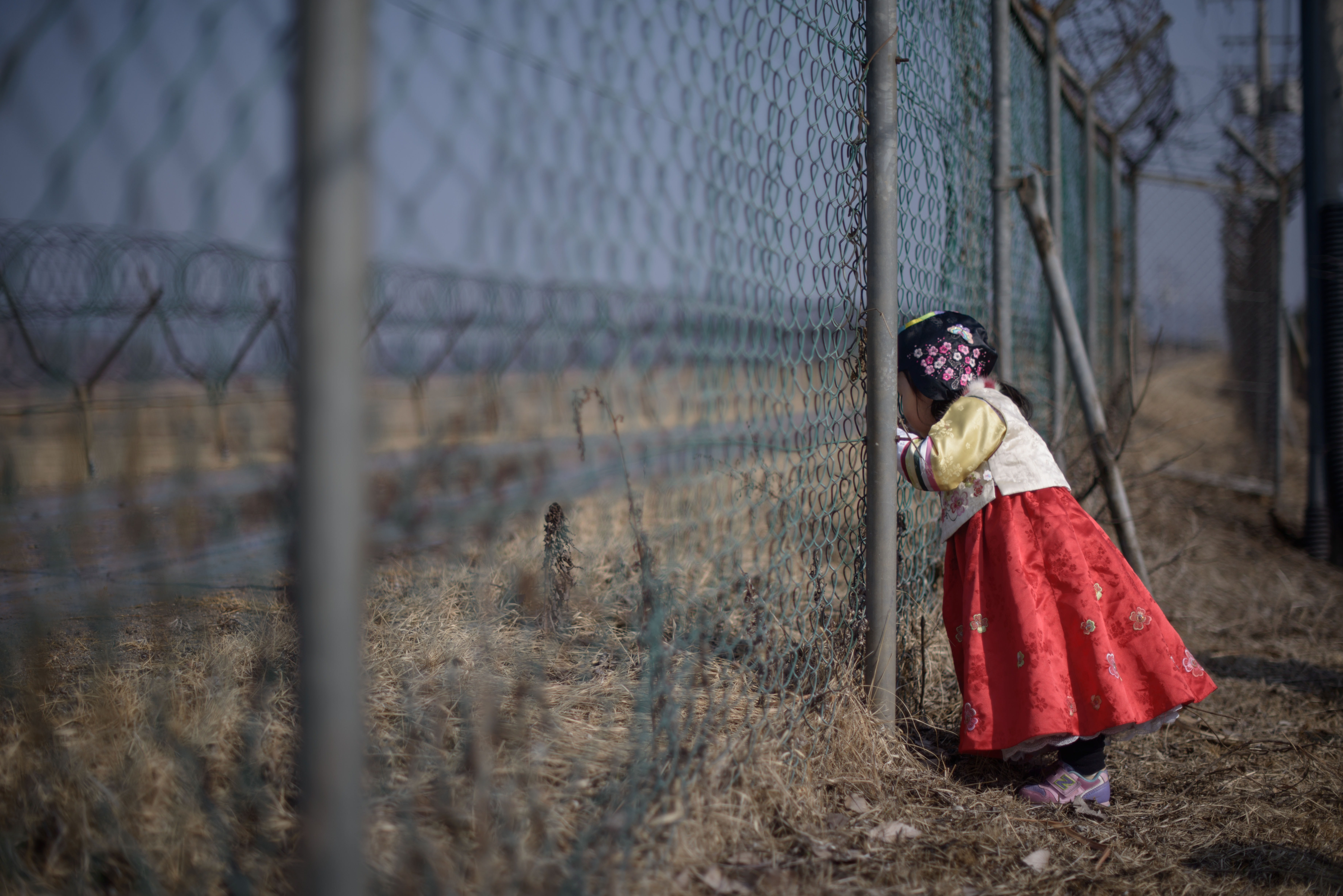A girl wearing a traditional hanbok dress stands at a military fence facing towards North Korea at Imjingak Park, south of the Military Demarcation Line and Demilitarized Zone (DMZ) separating North and South Korea, on Feb. 19, 2015. (Ed Jones/AFP/Getty Images)
